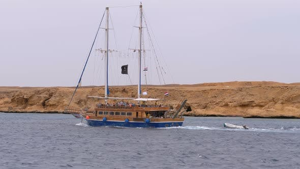 Thumbnail for Beautiful Tourist Yacht Sails in the Stormy Sea on the Background of Rocks. Egypt