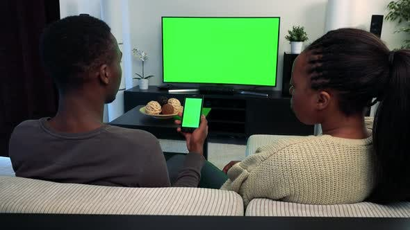 Thumbnail for Young Black Couple Watch Television in Living Room and They Work on Smartphone