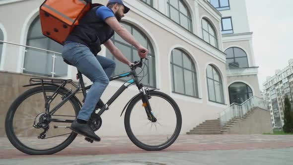 Courier with a Bag Rides a Bicycle to the Customer the Process of Delivering Food