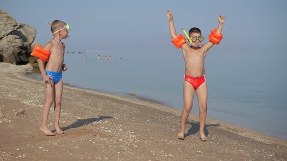 Family Vacation at the Sea. Boys on a Sandy Beach in Diving Masks and Life-saving Armbands Jump Up.