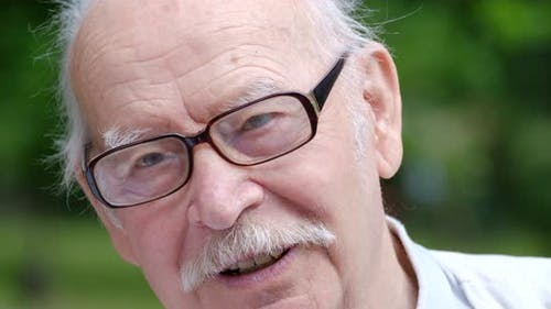 Grandpa with a Gray Mustache and Glasses Talks Cheerfully and Emotionally to the Camera