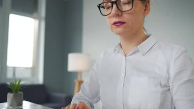 Woman with Glasses Typing on a Computer Keyboard