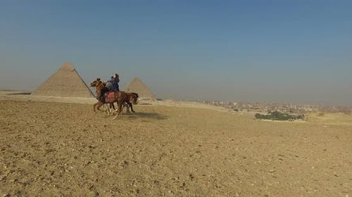 Young woman on horse galloping fast with local man at Giza pyramids complex