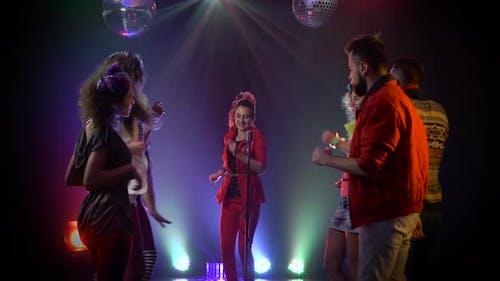Mädchen singt in ein Retro Mikrofon um Menschen tanzen zu singen. Rauchhintergrund