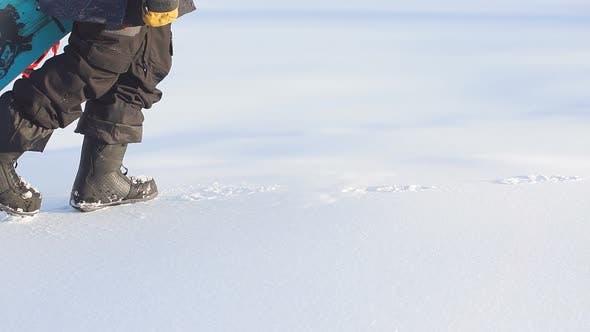 Waling Snowboarder on Slopes of Ski Resort