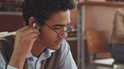 Mixed-Race Student in Earphones Scrolling at Smartphone