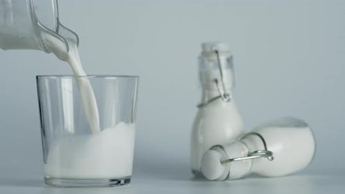 Milk Poured Into a Glass From a Jug