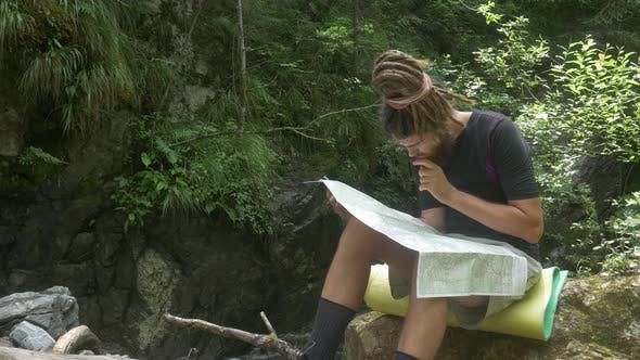 Traveler Considers Map in Forest