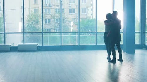 A Young Couple Dancing with Passion in a Studio with Smoke