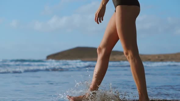 Thumbnail for Close-up of a Woman Walking Barefoot on the Beach and Enters the Ocean