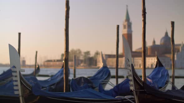 Cover Image for A Closeup of Covered Gondolas Swaying on a Pier Against the Blurred Venice View