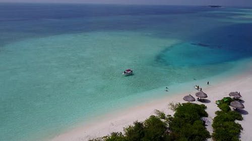 Tropical drone travel shot of a sunshine white sandy paradise beach and blue sea background in vibra