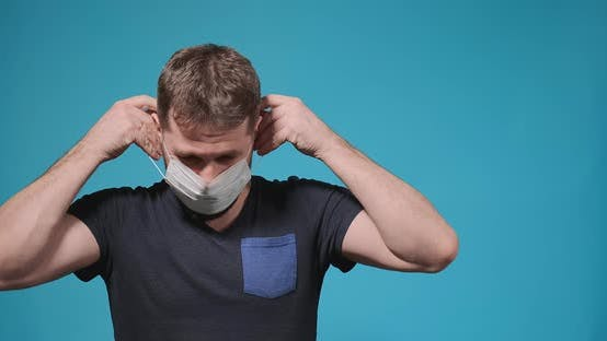 Guy with Beard Puts Disposable Medical Mask on and Breathes