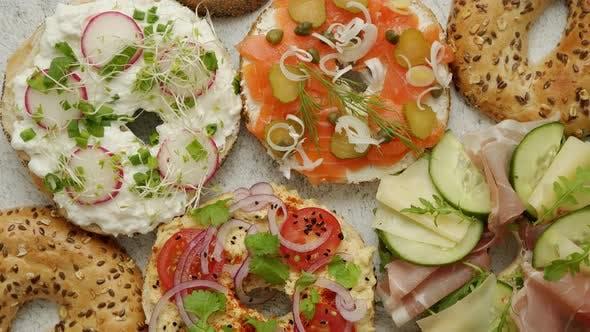 Bagel Sandwiches mit verschiedenen Belägen, Lachs, Hüttenkäse, Hummus, Schinken, Rettich und frischen Kräutern