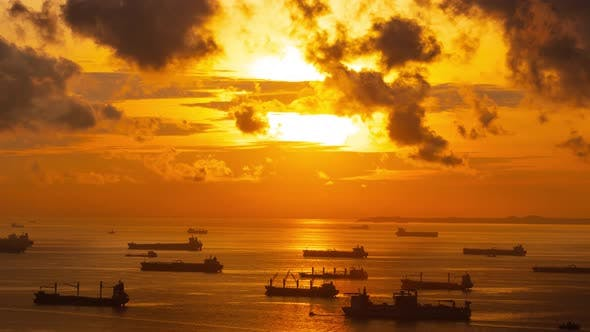 Sunrise time lapse of hundreds of cargo ships  off the coast of Singapore.
