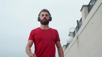 Man in an Athlete in Red Is Jogging in an Urban Environment