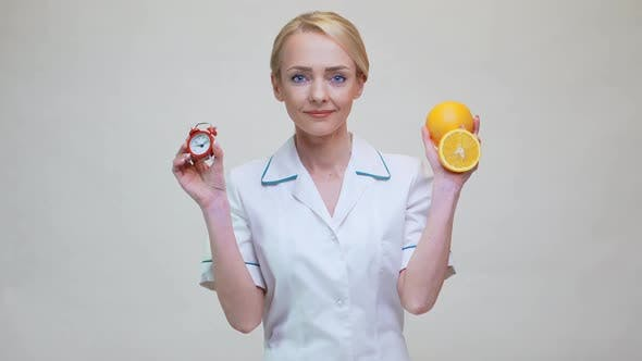 Thumbnail for Nutritionist Doctor Healthy Lifestyle Concept - Holding Orange Fruit and Alarm Clock