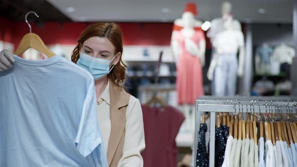Thumbnail for Portrait of Female Buyer in Protective Medical Mask and Gloves, Mask and Gloves Selects Clothes in