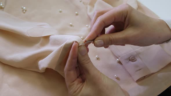 Thumbnail for Hands Cutting Button on Blouse Before Dry-cleaning