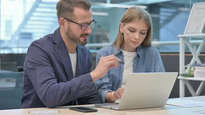 Businessman and Businesswoman Having Discussion on Laptop in Office
