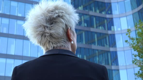 Thumbnail for A Middle-aged Businesswoman Looks at a Windowed Office Building - Closeup From Below