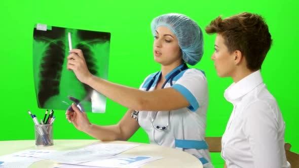 Der Arzt erzählt der Patientin von ihrer Diagnose, die ein Bild der Lunge betrachtet