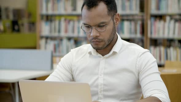 Thumbnail for Thoughtful Young Man Typing on Laptop in Library