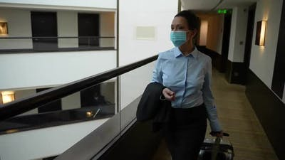 Adult Female Wearing Face Mask in Hotel Corridor