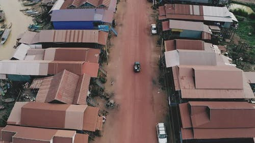 Aerial Tracking Shot of Moving Vehicle Driving Along Neighborhood During Sunset