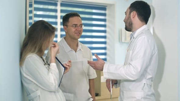 Cover Image for Male doctor holding tablet talking to two others doctors