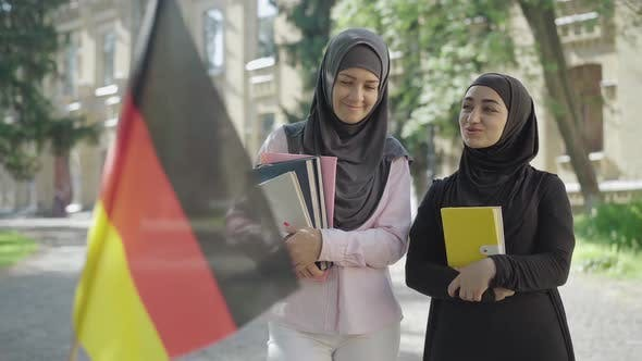 Two Female Muslim Immigrants Standing with Book on University Yard and Talking As Blurred German