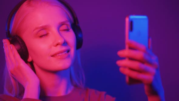 A Young Blonde Woman Listens to Music on Headphones Dances and Takes Pictures of Herself on the
