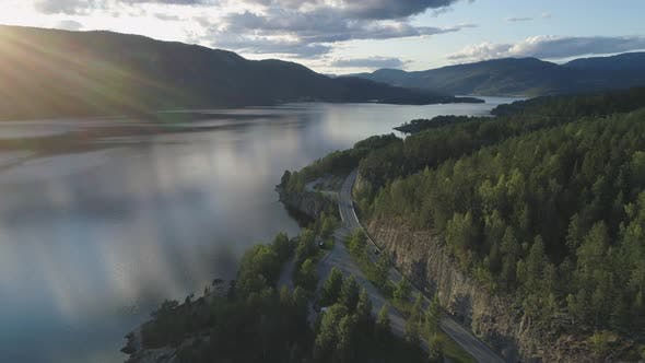 Thumbnail for Flying Over Road with Cars and Kroderen Lake Shore in Norway at Sunset. Aerial Reveal Shot