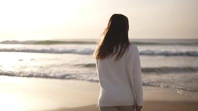 Brunette Woman Walks Alone on Sandy Beach
