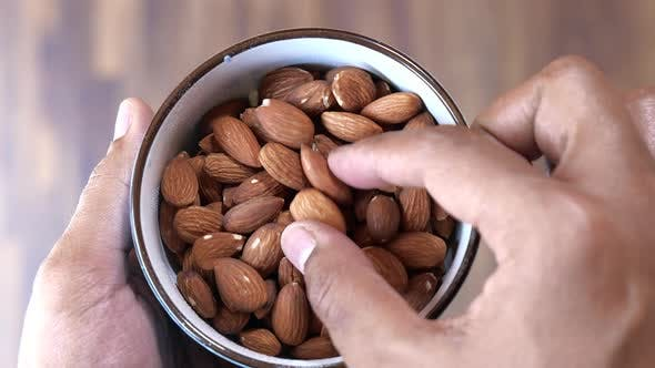 Thumbnail for Top View of Man Hand Picking Almond From a Bowl