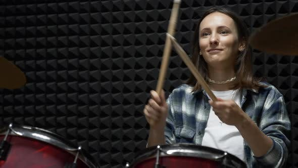 Thumbnail for Young stylish woman is playing drums during music band rehearsal in professional vocal studio