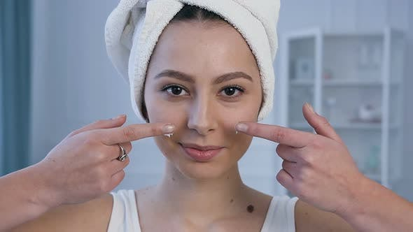 Cover Image for Portrait of Young Attractive Woman Applying Face Cream on the Cheekbones.