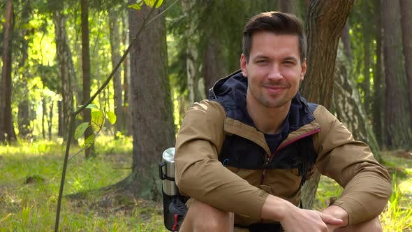 Thumbnail for A Young Hiker Sits on the Ground in Forest and Shows a Thumb Up To the Camera with a Smile