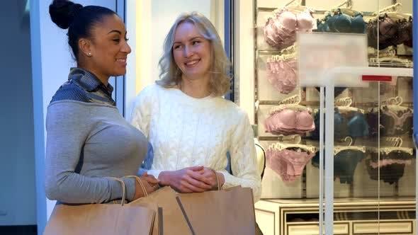 Women Discuss Bras and Panties Near the Lingerie Shop. Women Discuss Bras and Panties Near the