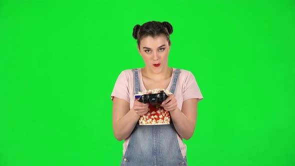 Thumbnail for Girl Playing a Video Game and Chews Popcorn on a Green Screen