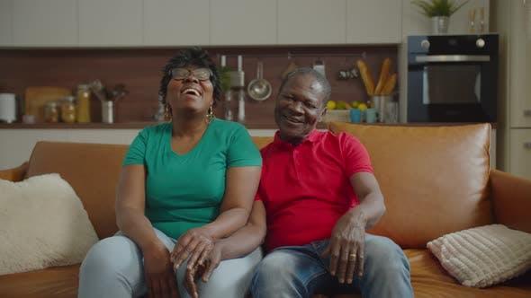 Positive Elderly African Couple Bonding on Sofa