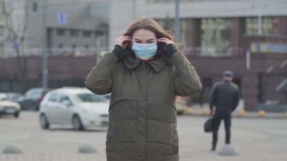 Thumbnail for Middle Shot of Young Brunette Woman Standing on City Street and Putting on Protective Mask