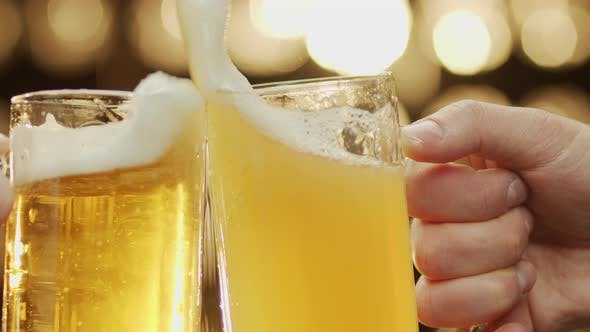 Close-up shot of two hands clinc beer spilling beer bokeh background