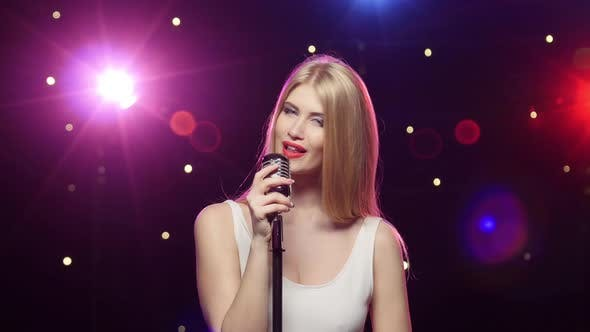 Cover Image for Blonde Girl Singing Into a Retro Microphone Strobe Lighting Effect