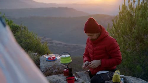 Man Traveller Makes Coffee in Camping Gear