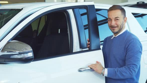 Thumbnail for A Smiling Man Opens the Doors of His New Car