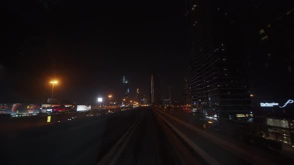 Dubai Metro Train Driving Past Skyscrapers in Urban City Center at Night