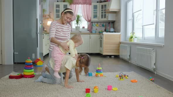 Thumbnail for Woman Mother Plays With Two Children Girls Toys In The Room