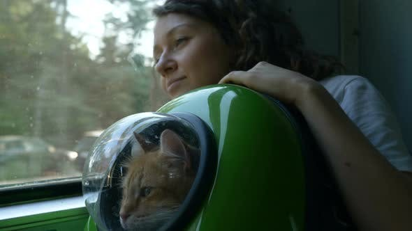 Thumbnail for Woman Rides a Train with a Red Cat in a Backpack with a Porthole
