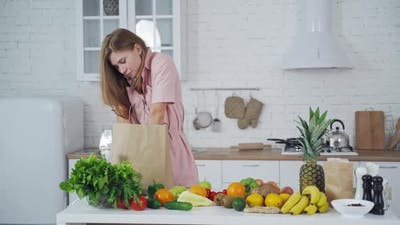 Woman unpacking grocery bag. Young woman with grocery shopping bag with fruits